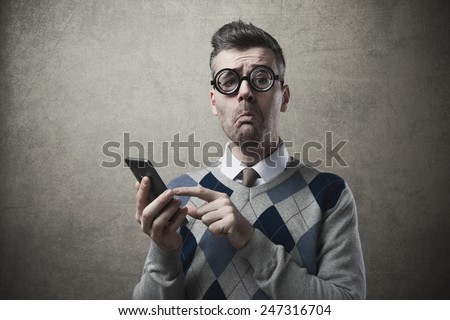 Funny clueless dumb guy having troubles with his smartphone - stock photo
