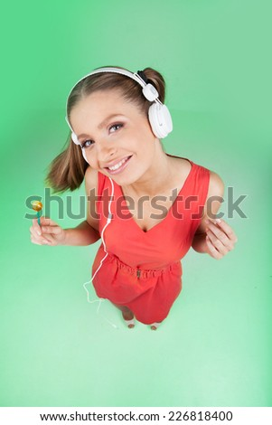 funny colorful girl listening music on green background. top view of woman listening to music on headphones and holding lollipop - stock photo