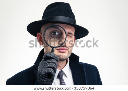 Funny concentrated inspector in black hat, coat and gloves looking through the magnifier over white background