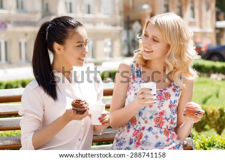 Funny conversation. Two young smiling girlfriends sitting in park and holding cupcakes with coffee.