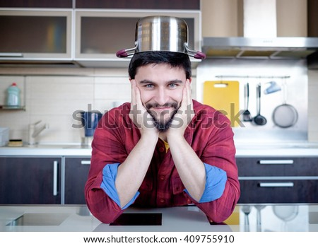 Funny cooking. Attractive caucasian man in the kitchen with pot on his head - stock photo