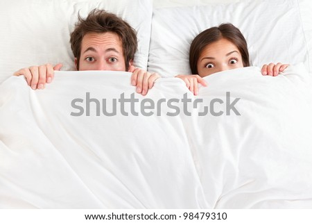 Funny couple in bed looking and peeking over sheets surprised. Young interracial couple, Asian woman, Caucasian man. - stock photo
