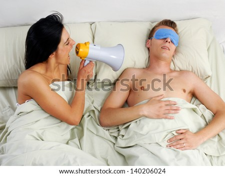 Funny couple in bed waking up in the morning.Using megaphone - stock photo
