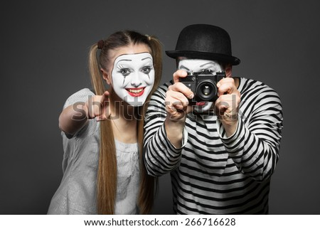 Funny couple of mimes taking a photo - stock photo