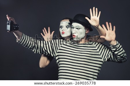 Funny couple of mimes taking a selfie photo  - stock photo