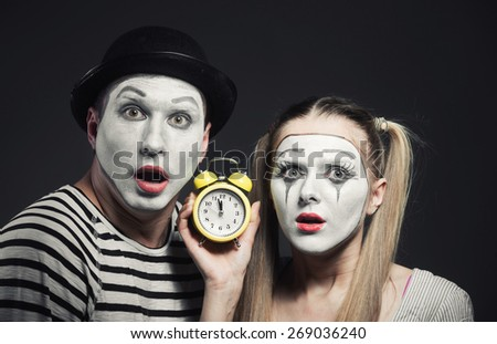 Funny couple of mimes with alarm clock looking at camera - stock photo