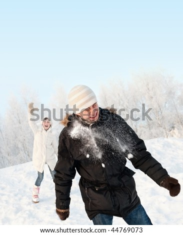 Funny couple playing snowballs - stock photo