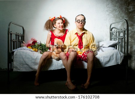 Funny couple sitting on the bed - stock photo