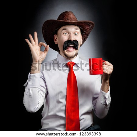 Funny Cowboy with big moustache showing OK gesture and holding red cup at black background - stock photo