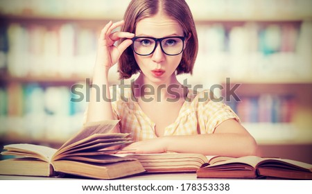 funny crazy  girl student with glasses reading books in the library - stock photo