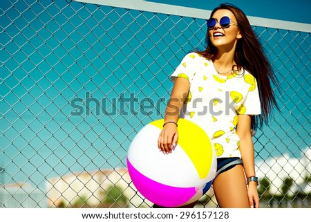 Funny crazy glamor stylish sexy smiling beautiful young woman model in  bright hipster summer casual cloth with colorful ball in the street behind blue sky - stock photo