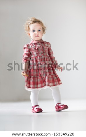 Funny curly baby girl in a red dress walking with a cookie in her hand