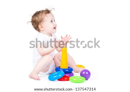 Funny curly baby playing with a plastic pyramid - stock photo