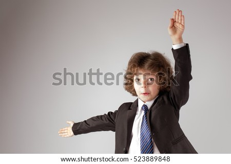 Funny curly boy showing marine alphabet. Gray background.