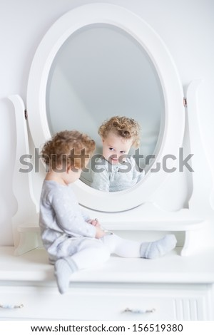 Funny cute baby girl watching her reflection in a white bedroom with a beautiful round mirror - stock photo