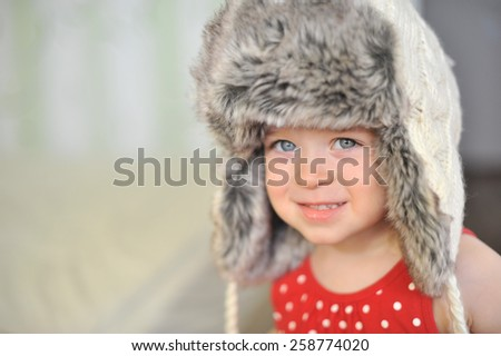 Funny cute baby girl with big blue eyes wearing a huge winter hat and a warm knitted jacket - stock photo