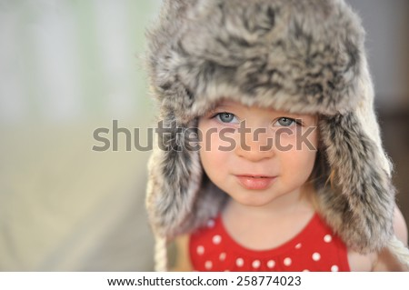 Funny cute baby girl with big blue eyes wearing a huge winter hat and a warm knitted jacket