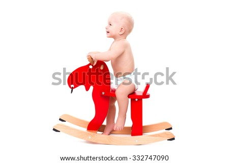 Funny cute baby sitting on the toy horse or elk and smiling - stock photo