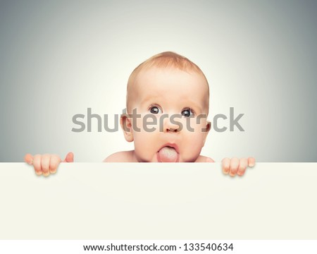 funny cute baby with white blank banner in hand isolated on a gray background - stock photo