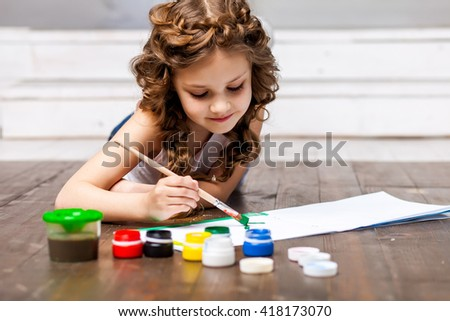 Funny cute cheerful little girl draws paints, the child sitting on the floor with a brush draws on the album, there are a number jar with colored paints, hairstyle with two pigtails - stock photo