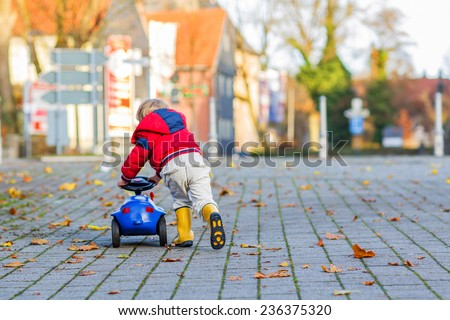 Funny cute child in red jacket driving blue toy car and having fun, outdoors. Kids leisure on cold day in winter, autumn or spring. - stock photo