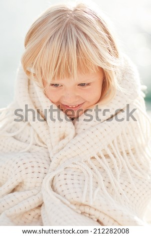Funny cute child wearing a huge knitted scarf - stock photo