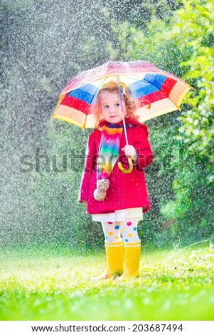 Funny cute curly toddler girl wearing red waterproof coat and yellow rubber boots holding colorful umbrella playing in the garden by rain and sun weather on a warm autumn or summer day  - stock photo