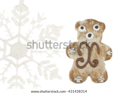 funny cute delicious gingerbread bear, decorated with sugar pattern and silver balls and white snowflake isolated on white background - stock photo