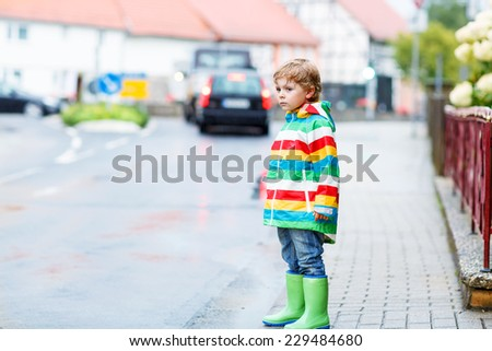 Funny cute kid boy walking in city through rain, wearing colorful rain coat and green boots outdoors at rainy day. Having fun.