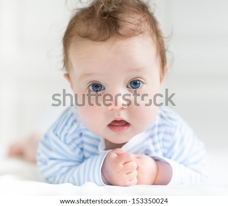 Funny cute little baby with big blue eyes playing on her tummy in a white nursery - stock photo