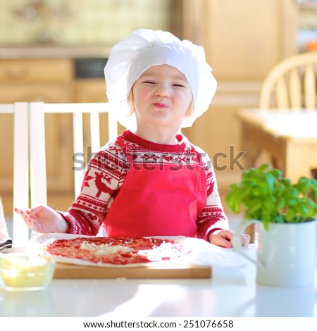 Funny cute little child, adorable toddler girl wearing red chef apron and white hat, preparing pizza topping it with tomato sauce, vegetables and cheese, sitting at dining table at bright sunny room - stock photo
