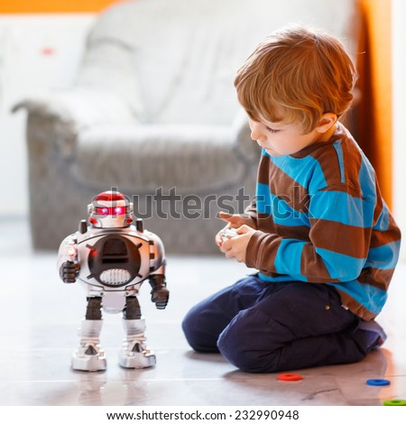 Funny cute little child playing with robot toy at home, indoor. Square format. - stock photo