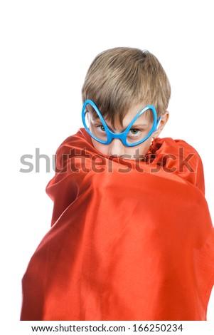 Funny cute little child pretending to be a superhero hiding in his cape (superhero concept) - stock photo