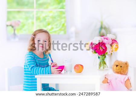 Funny cute little girl in a blue dress eating healthy breakfast - fruit, cereal and milk, feeding her toy bear in a white sunny kitchen