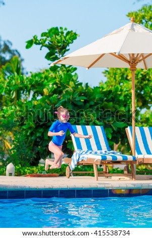 Funny cute little girl in outdoor swimming pool - stock photo