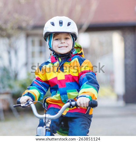 Funny cute  preschool kid boy in safety helmet and colorful raincoat riding his first bike and having fun on cold  day, outdoors. Active leisure with children in winter, sping or autumn.