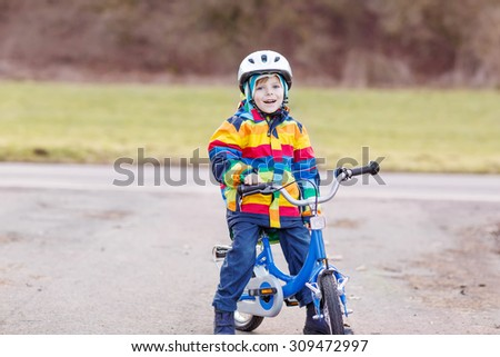 Funny cute  preschool kid boy in safety helmet and colorful raincoat riding his first bike and having fun on cold  day, outdoors. Active leisure with children in winter, spring or autumn.