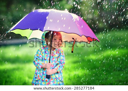 Funny cute toddler girl wearing waterproof coat with colorful umbrella playing in the garden by rainy and sunny day - stock photo