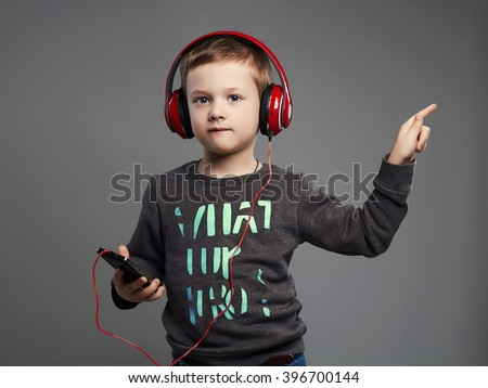 funny dancing child.little boy in headphones.fashionable kid listening music - stock photo