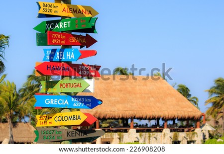 Funny direction signpost with distance to many different countries on Mexican coastline - stock photo