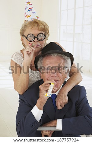 funny elderly couple in festivity blowing and making noise - stock photo