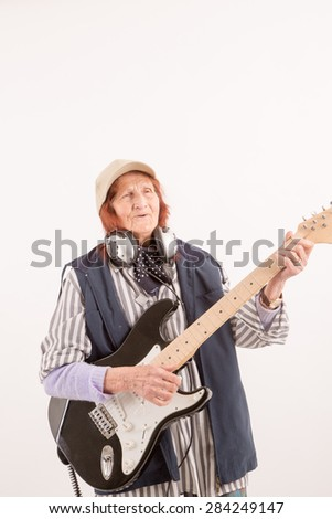 Funny elderly lady plays passionate electric guitar.