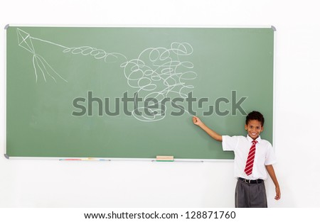 funny elementary schoolboy flying a impossible kite drawn on chalkboard - stock photo