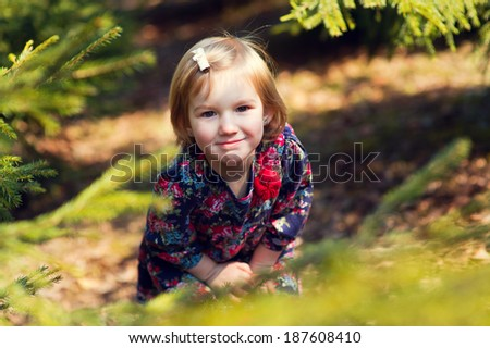 Funny european blond girl hides in green branches of fir tree