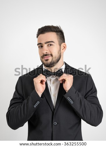 Funny excited groom adjusting his bow tie looking at camera. Desaturated portrait over gray studio background with retro vignette.  - stock photo