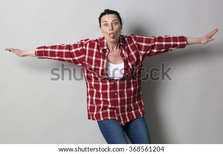 funny face concept - playful beautiful 40s woman sticking her tongue out with arms open like flying, studio shot - stock photo
