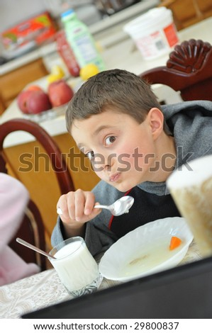 Funny face of the boy eating veggies - stock photo