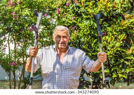 Funny faces of elderly octogenarian male triumphantly holding crutches on the patio of the house