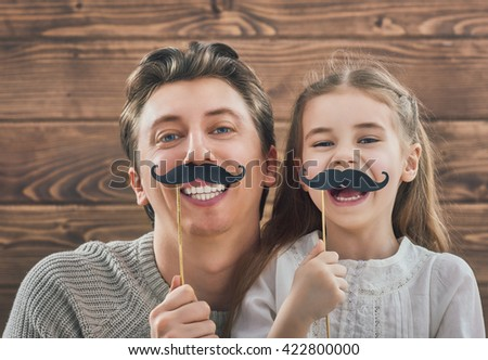 Funny family! Father and his child daughter girl with a paper accessories. Beauty funny girl holding paper mustache on stick. Beautiful young man holding paper mustache on stick. - stock photo