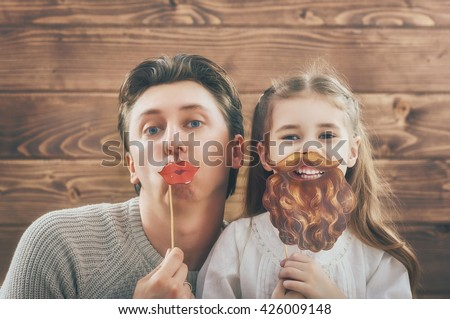 Funny family! Father and his child daughter girl with a paper accessories. Beauty funny girl holding paper beard on stick. Beautiful young man holding paper lips on stick. - stock photo